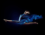 Artistic surreal photo of a beautiful woman in a dynamic front split in mid-air with flowing blue cloth wrapping her nude body on black background