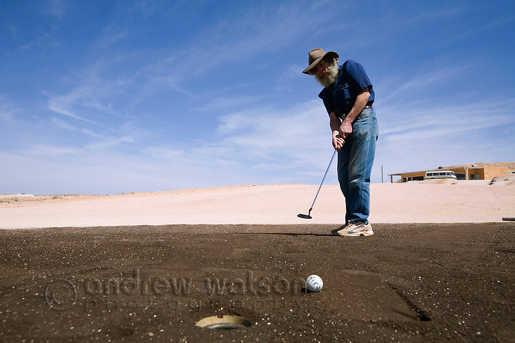 Making a putt at the Coober Pedy Opal Fields Golf Club.  The unique desert course is completely grassless with fairways of bare earth and putting greens made from oiled sand.  Coober Pedy, South Australia, AUSTRALIA.