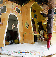 An art installation representing a full size figure about to enter a recreated house made of fabric and paper