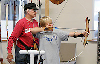 NWA Democrat-Gazette/DAVID GOTTSCHALK  Lovilla Dunlap (left) works with Russ Rogers, 11, on the archery range Thursday, October 22, 2015 at Rugged Faith in Tontitown. The church offers a free archery range prior to the activities of the evening.