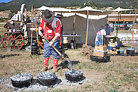 The 21st annual Lincoln County Cowboy Symposium was held in October 2010 at the Ruidoso Downs Racetrack in Ruidoso, New Mexico. Charles Wendt from the Rockin Dubya of Llano, Texas, tends his  Dutch ovens with the preferred kitchen utensil, a shovel.