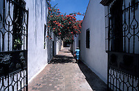 Woman walking down a narrow street i n old Santo Domingo, Dominican Republic. Santo Domingo's Zona Colonial was declared a UNESCO World heritage Site in 1990.