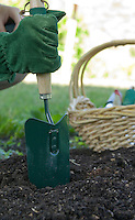 Photo of a gardener's gloved hand using a trowel on rich compost.