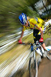 Female mountain biker in yellow jersey. Motion blur. Idaho. Model released.