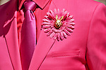 A man in the New York City Easter Parade wearing a bright pink suit and tie with a gold pin of a rabbit's head on the suit coat lapel