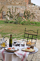 A typical Italian lunch with bruschetta, focaccia, a selection of cheeses with honey and a bottle of local wine served al fresco