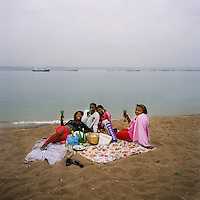 Teenage girls drink wine on the beach at Ilha de Luanda as they celebrate a friend's birthday.