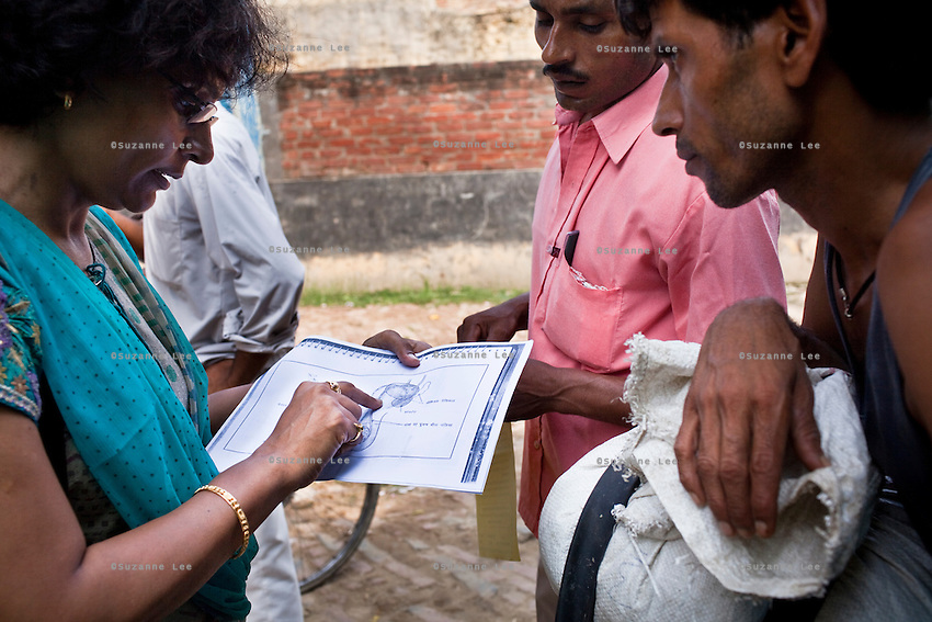 Jagroshan Sharma (aged 36, background (in grey) approaches random villagers from Shahpurjat village with Dr. Meenal Mehta (in blue), who is in charge of the USAID NSV projects in Ghaziabad, Uttar Pradesh, India. After doing NSV himself, he has been a star link worker introducing about 5 NSV cases per month since he started working part time under the tutelage of Dr Mehta. Jagroshan had chosen to do a non-scalpel vasectomy (NSV) for many reasons. He wanted to be an equal partner in the relationship, knew that NSV was less complicated and will not put his wife through numerous problems, and wants his two children to do well in life and study in English medium schools despite his modest earnings. Photo by Suzanne Lee / Panos London