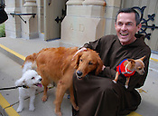 Fr. Michael Bertram, pastor of St. Francis of Assisi Church at 1927 N. 4th St. in Milwaukee, poses for photos on Saturday, Oct. 3, with the pets that owners brought for blessing in honor of St. Francis of Assisi. The dogs are, (from left) Dude, a Bichon who was accompanied by six-year-old Tatiana Osburn; Rocky, a Golden Retriever owned by Carmen and Pedro Mojica; and Chico, a Chihuahua owned by Hector Cruz. Ernie Mastroianni photo.