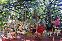 An 1850 carousel at Fete Paradiso (Fête Paradiso) on Governor's Island in New York seen on Saturday, August 17, 2013. The festival features 19th and early 20th century vintage French carnival rides and games from the collections of Francis Staub and Regis Masclet. The rides and games are museum quality and this is the first time they have been collected together in one place. Visitors will be able to ride many of them until the exhibit festival closes on September 29, (© Richard B. Levine)