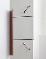A detail showing the built-in cupboards in the living room which have soft leather handles