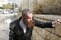 An Ultra-Orthodox Jewish man is trying to stand up after hit from a police water jet in Ramat Beit Shemesh West of Jerusalem on August 12 2013, after dozens of Haredim protest against desecration of ancient graves were discovered at a new housing construction site. Some 14 Ultra-orthodox Jews were arrested. Photo by Oren Nahshon