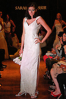 Model walks the runway in a Majestic wedding dress - silk taffeta V-neck gown with beaded tulle overlay, by Sarah Jassir, for the Sarah Jassir Couture Bridal Fall 2012 Opulence collection.