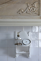 A detail of one of the ornate kitchen cupboards made from salvaged wood panels; underneath a tiny carved shelf holds a clock and a jar of herbs