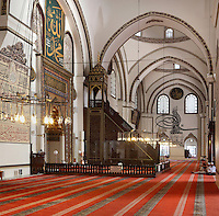Mihrab and minbar of the Grand Mosque or Ulu Cami, built 1396-99 under the Ottoman Sultan Bayezid I by the architect Ali Neccar in the Seljuk style, Bursa, Turkey. The mosque has 192 monumental wall inscriptions written by the famous calligraphers of that period. The mosque is a large rectangular building with 2 minarets, and 20 domes supported by 12 columns. Supposedly the 20 domes were built instead of the 20 separate mosques which Sultan Bayezid I had promised for winning the Battle of Nicopolis in 1396. The dome over the sadirvan is capped by a skylight creating a soft light which illuminates the large building. The mosque is in the old city centre of Bursa and remains the largest mosque in the city. Picture by Manuel Cohen