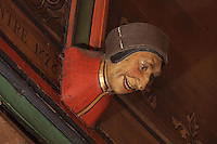 Carved and painted roof bracket with head of a laughing man, architectural detail of the painted wooden ceiling in the shape of a boat's hull, in the Salle des Povres or Room of the Poor, almost 50m long, in Les Hospices de Beaune, or Hotel-Dieu de Beaune, a charitable almshouse and hospital for the poor, built 1443-57 by Flemish architect Jacques Wiscrer, and founded by Nicolas Rolin, chancellor of Burgundy, and his wife Guigone de Salins, in Beaune, Cote d'Or, Burgundy, France. The hospital was run by the nuns of the order of Les Soeurs Hospitalieres de Beaune, and remained a hospital until the 1970s. The building now houses the Musee de l'Histoire de la Medecine, or Museum of the History of Medicine, and is listed as a historic monument. Picture by Manuel Cohen