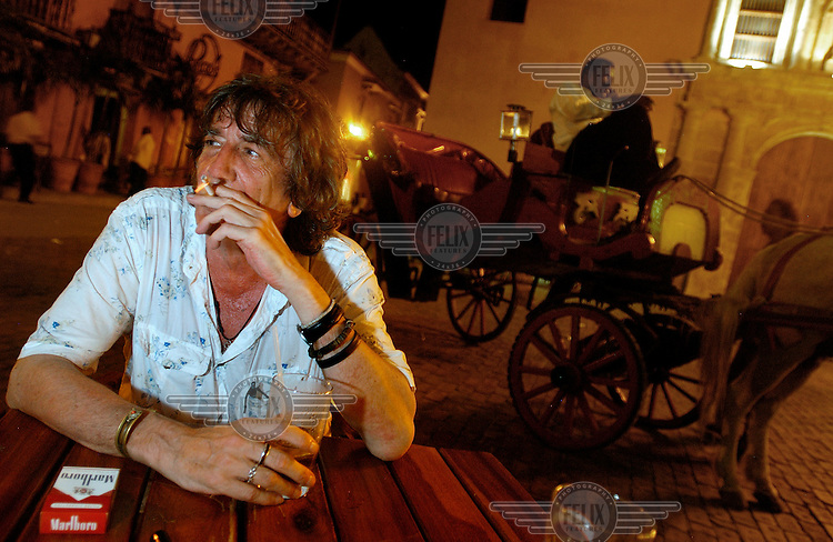 Howard Marks smokes and drinks in Cartagena's Santo Domingo Plaza next to a horse drawn cart. Marks, a former large-scale marijuana smuggler, convicted criminal and bestselling author is in town to research and write about Cartagena.