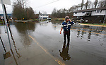 Phillip Joe talks on his cell phone as he stands in a pool of water on the main road in front of his home on the Cowichan First Nation Reserve along Tzouhalem Road, the day after a state of emergency was called due to the flooding, in Duncan, BC, British Columbia, Canada. Photo assignment for the Canadian Press (CP).