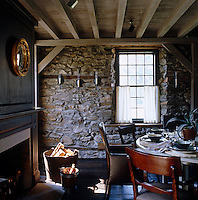The Connecticut fieldstone has been left exposed on the dining room wall and the room is furnished with English Regency dining chairs and a contemporary Swedish table