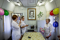 The crew of the Matvei Mudrov train celebrates the birthday of the medical director, Vera Chebakova. A portrait of Doctor Matvei Mudrov, after whom the train was named. hangs on the wall above the table. <br /> <br /> The Matvei Mudrov train is a medical train operated by Russian Railways along the course of the Baikal Amur Magistral (Baikal-Amur Mainline, or BAM) railway line. Named after a famous 19th century Russian physician, the train employs around 15 doctors who make about 10 trips a year, each lasting two weeks. Along the way they deliver essential medical services to people living in remote villages along the 4,324 km long BAM railway. Though not equipped to carry out surgical procedures the train has heart monitors, ultrasound and x-ray machines to deliver diagnosis.