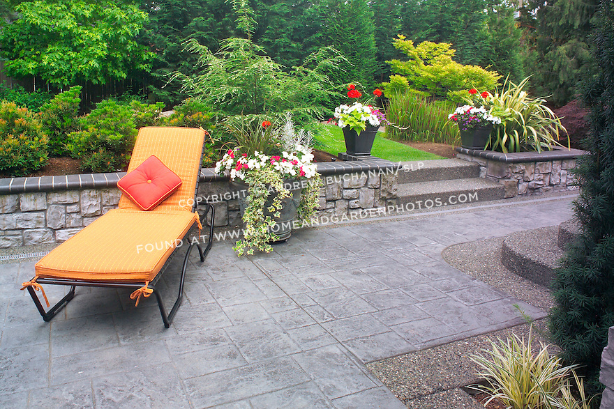 Bold colors on the chair and lounge cushions add drama to an otherwise peaceful, verdant design.  Narrow entries through the retaining wall, such as for the stairs, help hide the rear walking garden from view and add mystery and depth to the space. Design by Sander Groves landscapes, Inc.