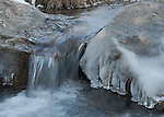 Ice forming along the edges of the rocks on the creek on a cold day