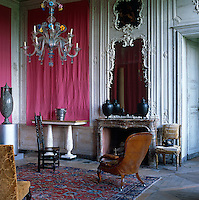 The Salon Indien with its chandelier of Murano glass has a mirrored boiserie fireplace and the walls are lined with pink Indian fabric
