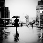 A business man holding a black umbrella standing in the city in the pouring rain.