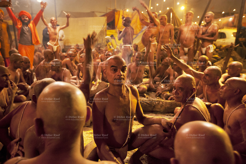"""India. Uttar Pradesh state. Allahabad. Maha Kumbh Mela. Hindu holy men of the Juna Akhara sect participate in rituals that are believed to rid them of all ties in this life and dedicate themselves to serving God as """"Naga"""" or naked holy men. A group of Naga Sadhus with a seer dressed with orange clothes and turban at night in Sangam. The Kumbh Mela, believed to be the largest religious gathering is held every 12 years on the banks of the 'Sangam'- the confluence of the holy rivers Ganga, Yamuna and the mythical Saraswati. The belief is that bathing and taking a holy dip will wash and free one from all the past sins, get salvation and paves the way for Moksha (meaning liberation from the cycle of Life, Death and Rebirth). In Hinduism, Sadhu (good; good man, holy man) denotes an ascetic, wandering monk. Sadhus are sanyasi, or renunciates, who have left behind all material attachments. They are renouncers who have chosen to live a life apart from or on the edges of society in order to focus on their own spiritual practice. The significance of nakedness is that they will not have any worldly ties to material belongings, even something as simple as clothes. This ritual that transforms selected holy men to Naga can only be done at the Kumbh festival. A Sadhu is usually referred to as Baba by common people. The Maha (great) Kumbh Mela, which comes after 12 Purna Kumbh Mela, or 144 years, is always held at Allahabad. Uttar Pradesh (abbreviated U.P.) is a state located in northern India. 6.02.13 © 2013 Didier Ruef"""