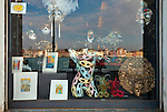 A shop with Carnival masks at the Giudecca, with the skyline of downtown Venice reflected in the window.