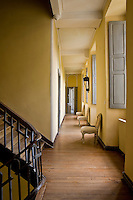 Grey painted shutters punctuate the yellow walls of this long corridor on the first floor