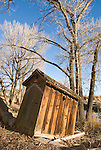 Collapsing and leaning outhouse by the creek, winter, rural Nevada