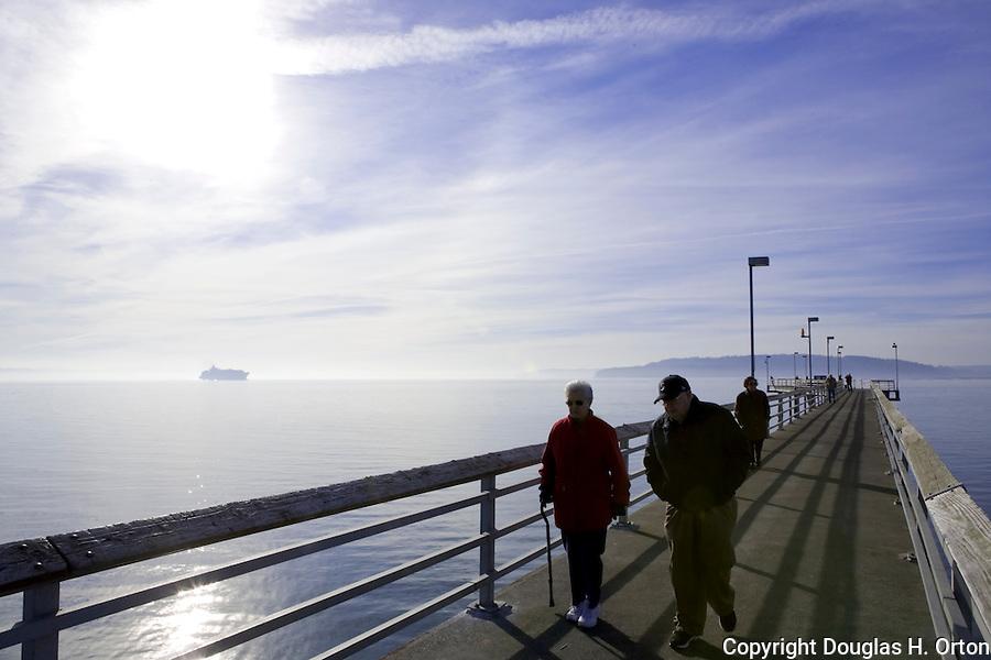 Seniors enjoy sunny winter afternoon walking on fishing for Seattle fishing pier