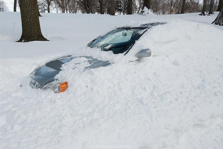 A car is buried by snow thrown from a passing plow following a snow storm.