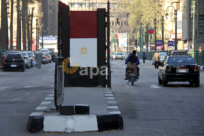 Egyptians walk past a gate at Al-Qasr Al-Aini street in downtown Cairo, February 10, 2014. A concrete wall blocking Qasr Al-Aini street which set to prevent protesters or rioters entering streets leading to the nearby interior ministry, parliament and government headquarters, has been replaced with a gated metal barrier. Photo by Mohammed Bendari