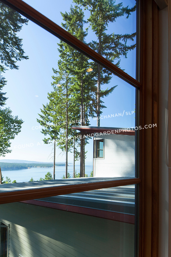 A window looks out to the Salish Sea across the metal roof of a contemporary home. This image is available through an alternate architectural stock image agency, Collinstock located here: http://www.collinstock.com