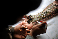 Before the wedding of British/Punjabi couple Lindsay and Navneet Singh, henna patterns are applied to the hands and arms of the bride.