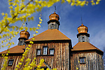 Ancient wooden church house under blue sky. Pirogovo, Ukraine, Eastern Europe springtime countryside scenic.