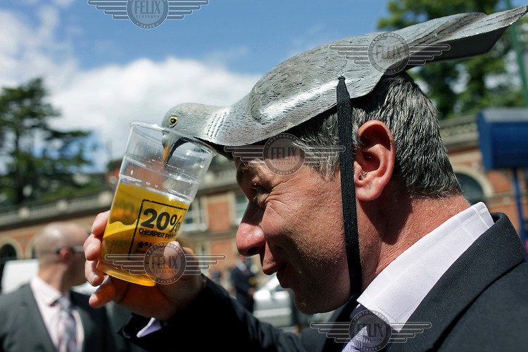 A man wearing a novelty hat in the shape of a pigeon during the Royal Ascot race meeting. The annual event, during which each day begins with the Queen's arrival in a horse drawn carriage, dates back to 1711 when Queen Anne organised the first races on what was then a heath near Windsor Castle.