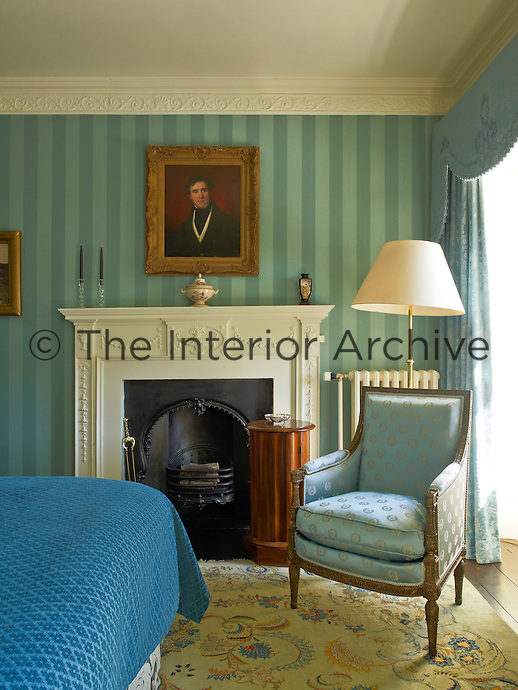 Striped green wallpaper depth to this guest bedroom in a restored Georgian country house