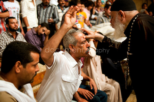 A devoted Copt receives exorcism session, performed by Father Samaan in Mokattam. After throwing holy water on the face of the devoted, Father Samaan gently blows on the forehead while drawing a sign of the cross with his finger.<br /> copyright : Magali Corouge / Documentography