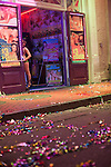 """A woman peers out from behind the doorway of an adult nightclubs on Bourbon Street in New Orleans's French Quarter.  After Madden Gras, colored ribbons line the foreground.  EA Sports, creator of the popular """"Madden NFL"""" game, celebrates the release of the 2011 game edition with Madden Gras 2011, starring the New Orleans Saints.  Madden Gras 2011 culminates with a Mardi-Gras-style parade through the French Quarter of New Orleans to Jackson Square."""