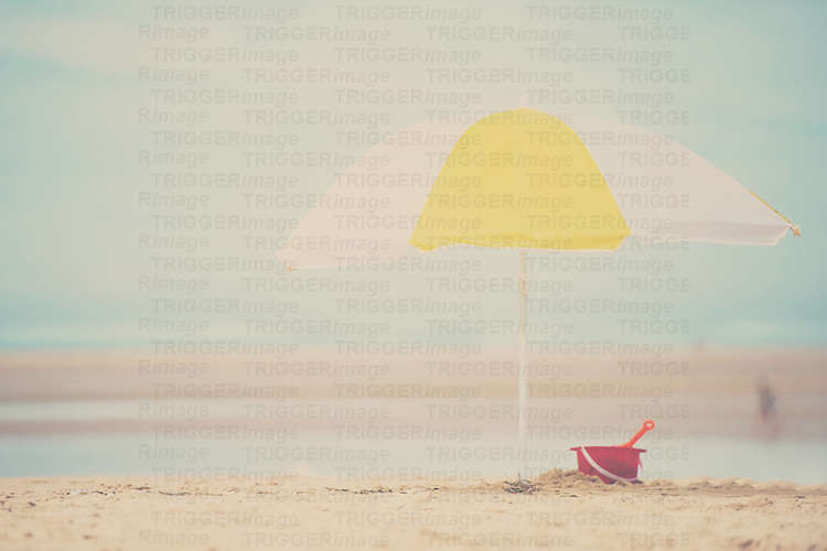 a yellow and white beach umbrella with a plastic bucket and spade beneath it