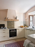 A splash back of iridescent pale grey tiles with a  brightly patterned section behind the cooker runs along the kitchen wall