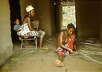 Women of Kpelle tribe socializing inside hut, young one at right weaving mat, woman at left carrying baby strapped on her back, Liberia, West Africa.