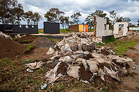 Bags of soil containing small amounts of gold sit slashed and abandoned after police forced illegal gold miners to destroy them on the outskirts of Johannesburg, South Africa. Behind the bags is what is left of the judo studio which operated in Durban Deep for over two decades. During the previous few weeks, all the power cables in the area were dug up and stolen, leaving the entire area without any power.