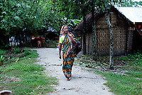 Shahida Begum, 35, walks to work in her village, Palashbari Villlage, Taragonj, Rangpur, Bangladesh on 18th September 2011. She has found financial independence and contributes to the family income by working as a saleswoman, earning 3500 - 5000 Bangladeshi Taka per month. She is one of many rural Bangladeshi women trained by NGO CARE Bangladesh as part of their project on empowering women in this traditionally patriarchal society. Named 'Aparajitas', which means 'women who never accept defeat', these women are trained to sell products in their villages and others around them from door-to-door, bringing global products from brands such as BATA, Unilever and GDFL to the most remote of villages, and bringing social and financial empowerment to themselves.  Photo by Suzanne Lee for The Guardian