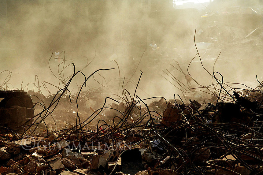 Dust rises from the rubble as the bulldozers move in.