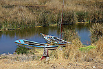 South America, Bolivia, Kala Uta Island. Aymara woman and boats on Kala Uta Island of Lake Titicaca.
