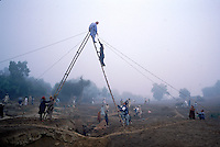 Mark Kenoyer on specially designed bipod ladder at Harappa site, Pakistan.  4,800 years ago, at the same time as the early civilizations of Mesopotamia and Egypt, great cities arose along the flood plains of the Indus and Saraswati (Ghaggar-Hakra) rivers.  Developments at Harappa have pushed the dates back 200 years for this civilization, proving once and for all, that this civilization was not just an offshoot of Mesopotamia..They were a highly organized and very successful civilization.  They built some of the world's first planned cities, created one of the world's first written languages and thrived in an area twice as large as Egypt or Mesopotamia for 900 years (1500 settlements spread over 280,000 square miles on the subcontinent)..There are three major communities--Harappa, Mohenjo Daro, and Dholavira. The town of Harappa flourished during this period because of it's location at the convergence of several trade routes that spanned a 1040 KM swath from the northern mountains to the coast.